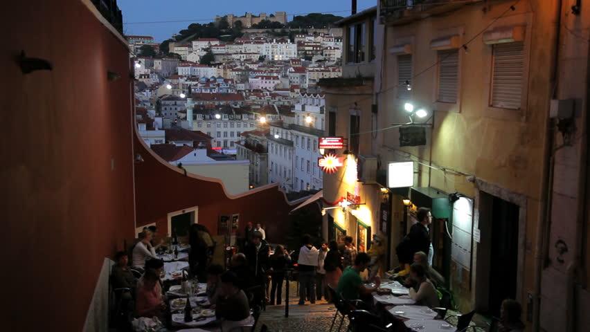 Portugal - June 2012: People eating outside a Lisbon restaurant at dusk in Barrio alto