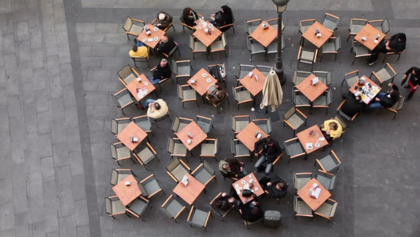 Several people sit at cafe tables on street, (view from above)