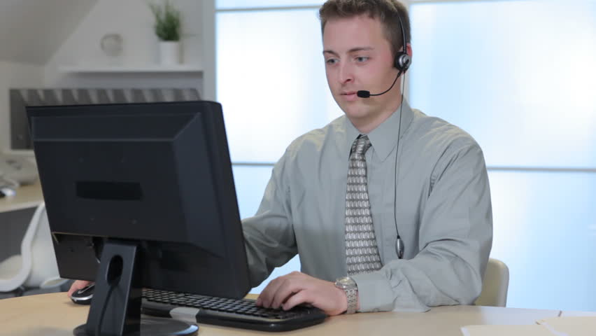 Mid adult female receptionist working on computer and speaking on portrait of business man in office with headset hd stock video clip sciox Images
