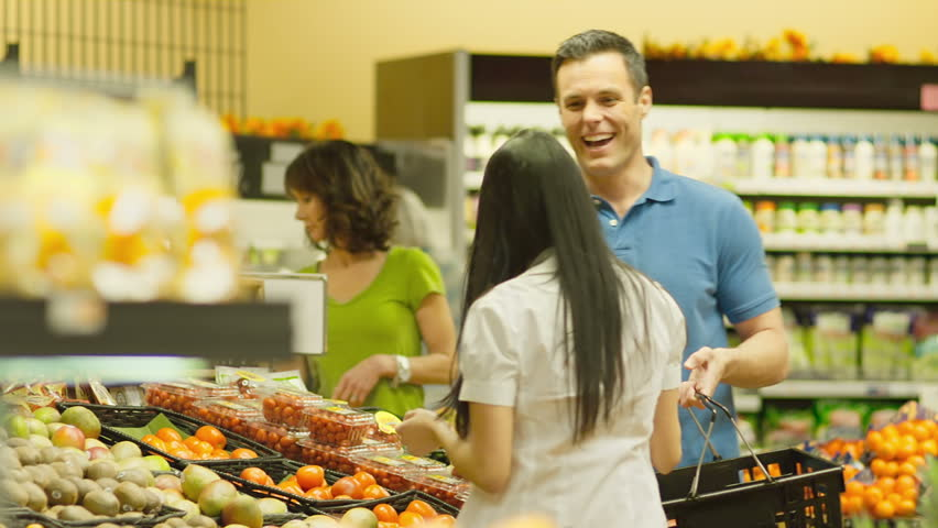 A young couple walk around a pick out healthy produce products together in a grocery store. Wide shot.