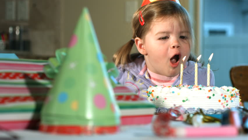 Little girl blowing out birthday candles, slow motion