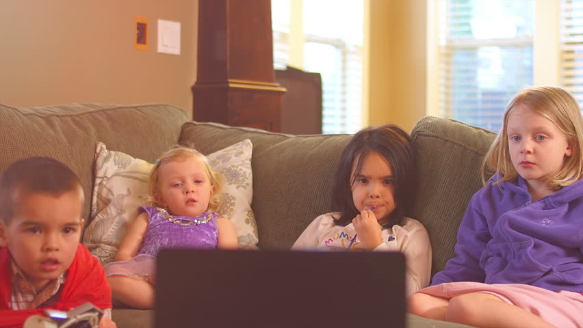 A group of cute little kids sit together watching something on a laptop. Wide shot.