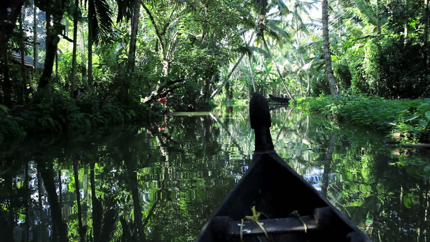 Traditional river canoe POV traveling through tropical backwaters in Alleppey, Kerala India