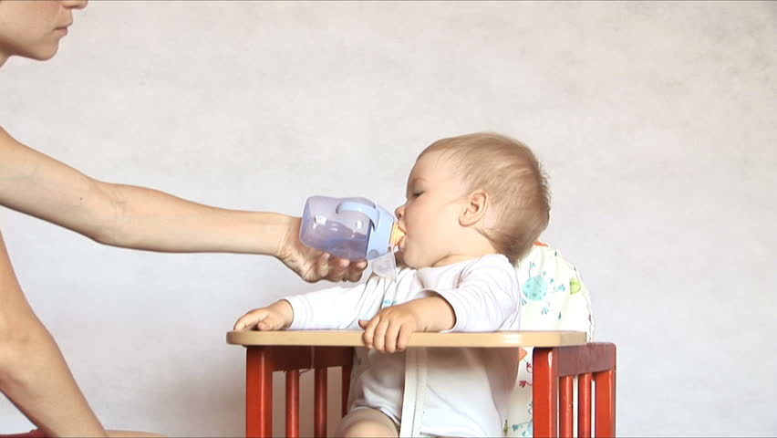 Baby sits at a children's little table. Mum gives to drink water of the child. Isolated on the white.