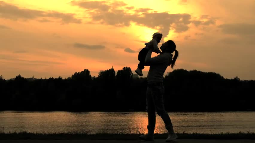 Silhouettes of young woman lifting small girl | Shutterstock HD Video #4673360
