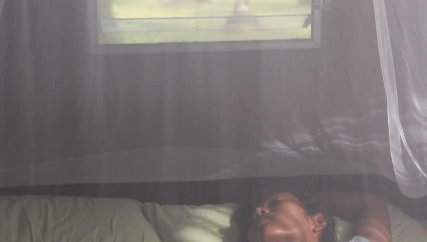 woman sleeping under a mosquito net