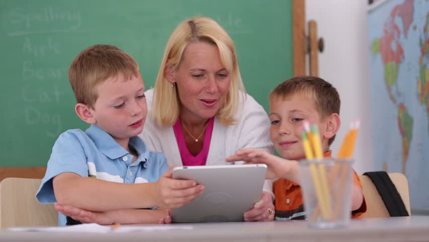 Teacher at school uses digital tablet in classroom