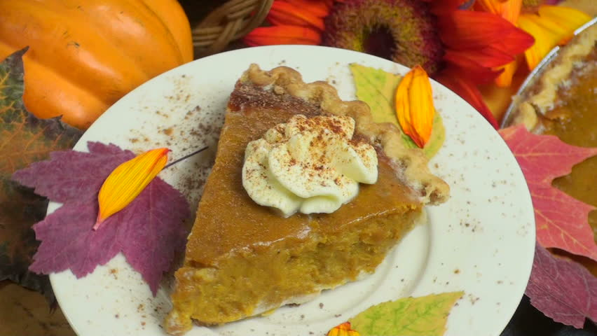 Slice of pumpkin pie, topped with whipped cream, displayed, rotating, above festive holiday background of whole pie, fall leaves, red sunflower, squash.