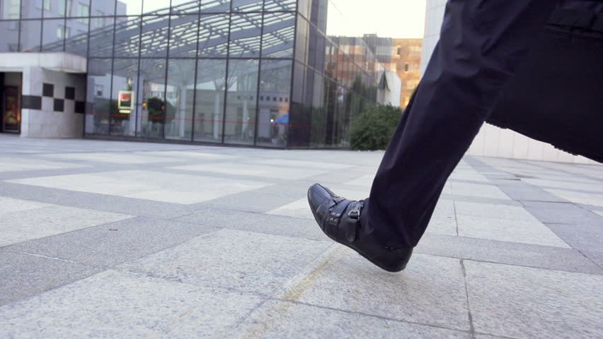 Slow Motion Rear View Shot Of A Male Legs Walking Through Business Area.