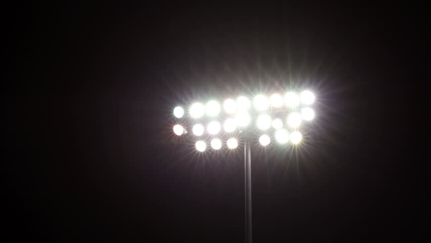 Isolated shot of stadium flood lights turning on a black sky background