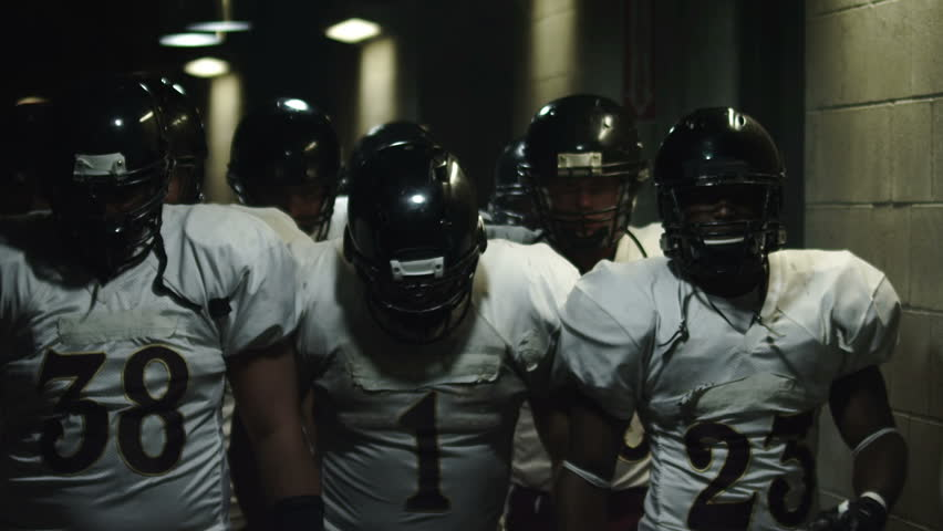 Football team walks down a dark tunnel towards the field before a game | Shutterstock HD Video #4706294