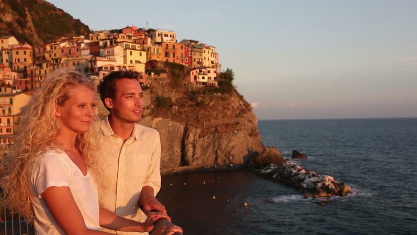 Couple in love by sunset on holidays travel. Romantic young beautiful couple enjoying ocean view romance. Young people, man and woman traveling on vacation in Manarola, Cinque Terre, Liguria, Italy