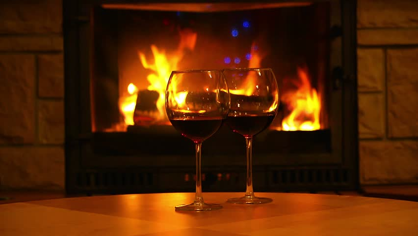 Glasses Of Wine On The Table In Front Of Flames Of Fireplace ...