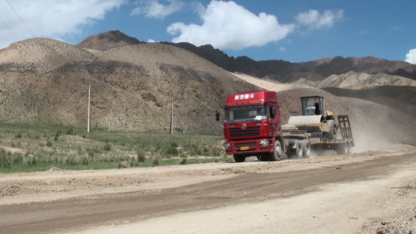 NARYN TO BISHKEK ROAD, KYRGYZSTAN - 24 JULY 2013: A Chinese truck carrying heavy machinery drives over a road in Kyrgyzstan, that is being upgraded by Chinese road crew