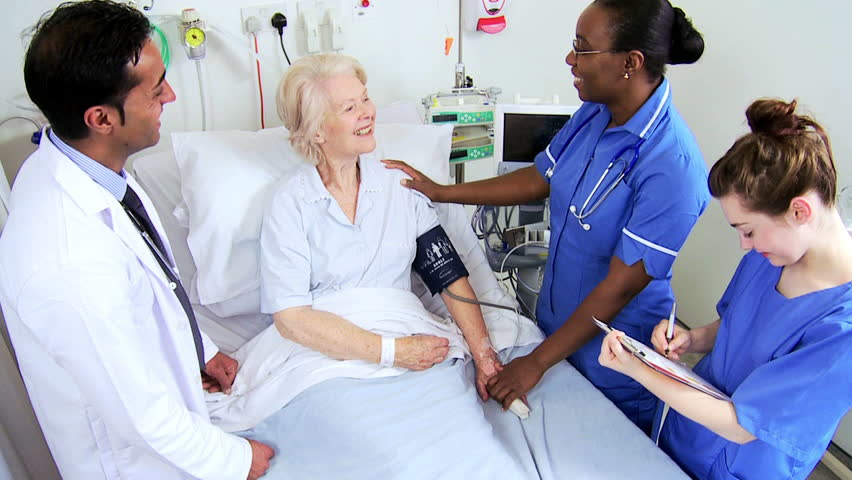 African American Nurse Taking Blood Pressure Of An Elderly ...