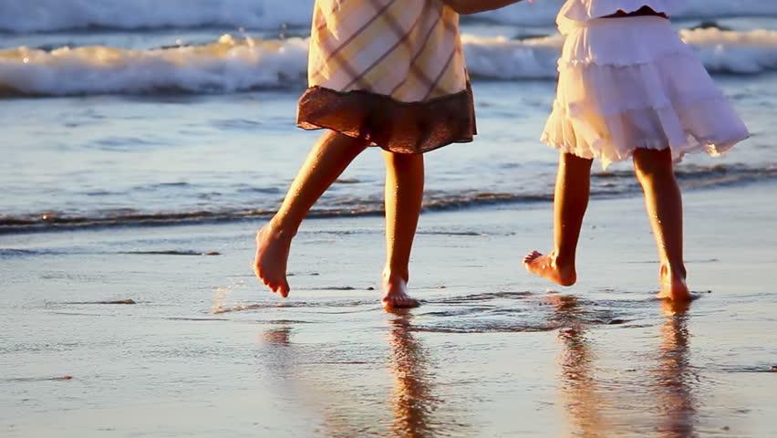 Men hold down girl on beach