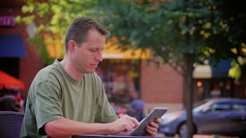 A man uses a tablet computer outside at Market Square in downtown Pittsburgh Pennsylvania.