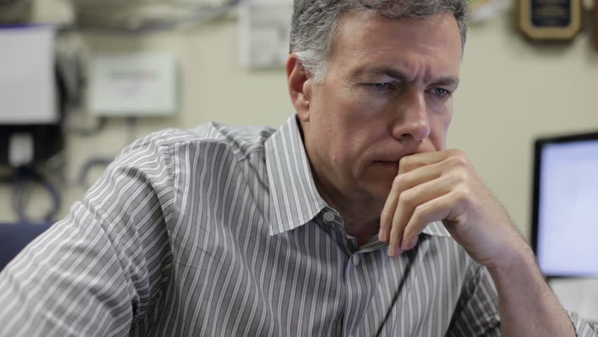 A pensive mature man sitting in his office at work.