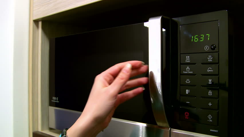 Woman using a microwave in the kitchen - slider shoot