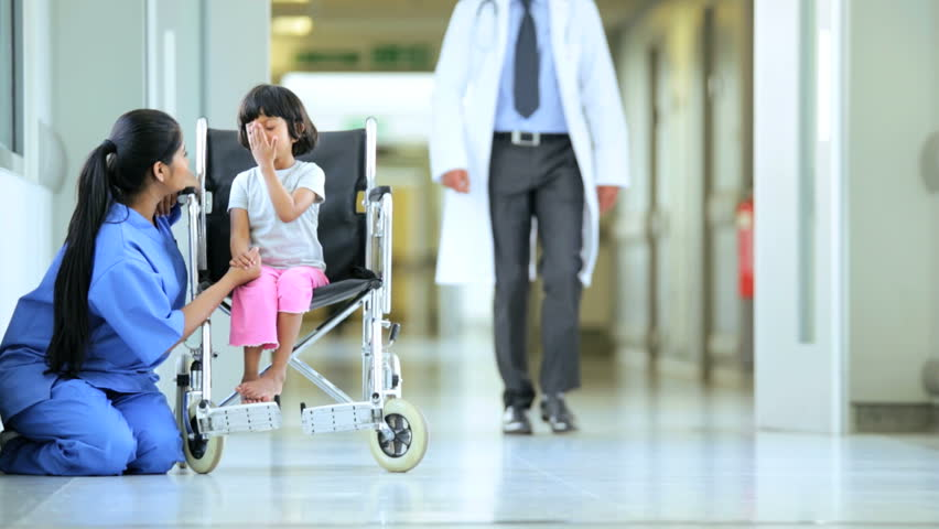 South Asian physician and nurse cheering up young patient wheelchair waiting for hospital treatment