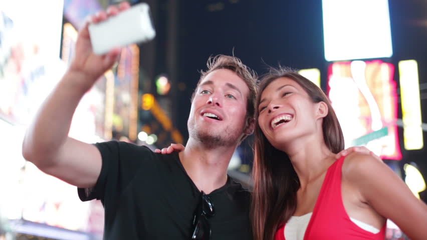 Dating young couple happy in love taking self-portrait photo on Times Square, New York City at night. Beautiful young multiracial tourists having fun date, Manhattan, USA. Asian woman, Caucasian man. | Shutterstock HD Video #4814159
