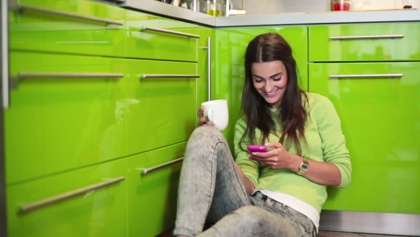 Young woman sitting on floor in kitchen and texting on smartphone