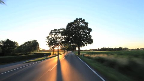 Driving a car on a sunny day on a road into the sunset, Point of View - POV, with a roof-mounted, Germany.