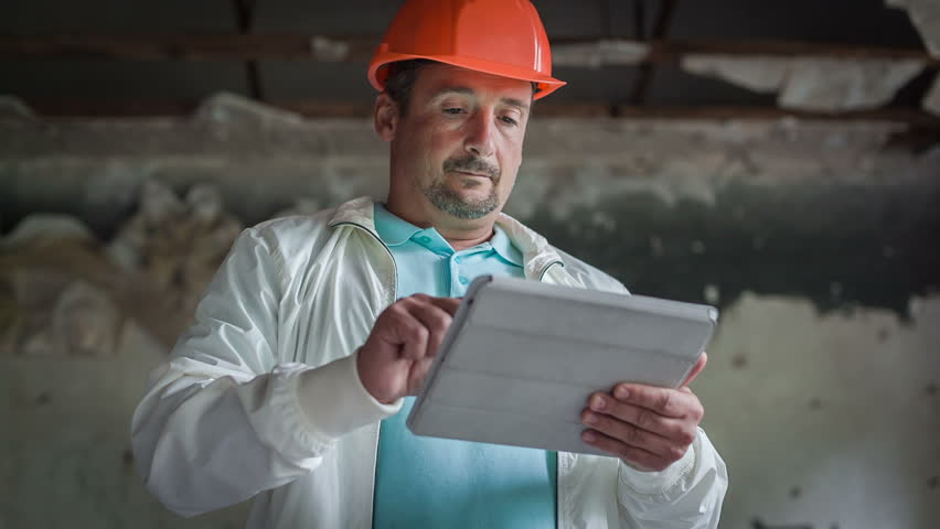 the engineer is getting acquainted with the economic calculations on the tablet. RAW Video 6