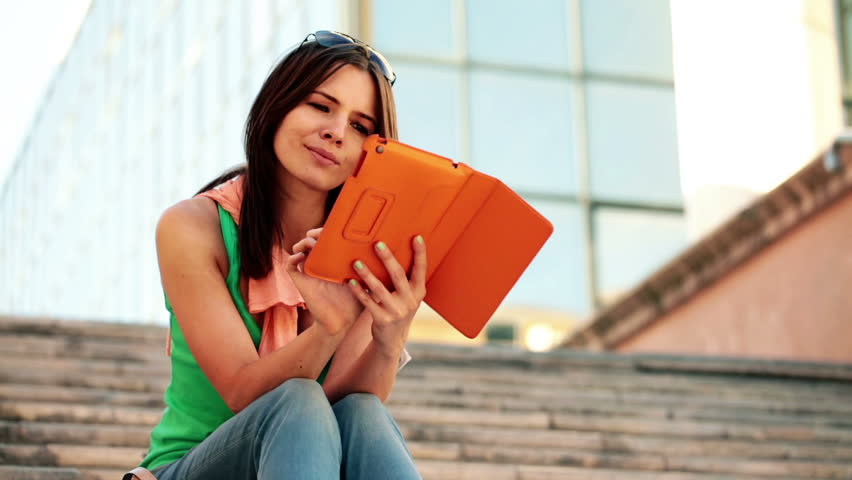 Portrait of young happy woman with tablet computer in the city