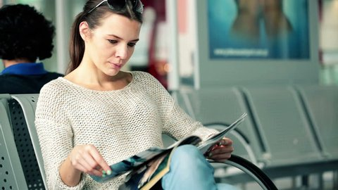 Beautiful woman reading fashion magazine in airport waiting room