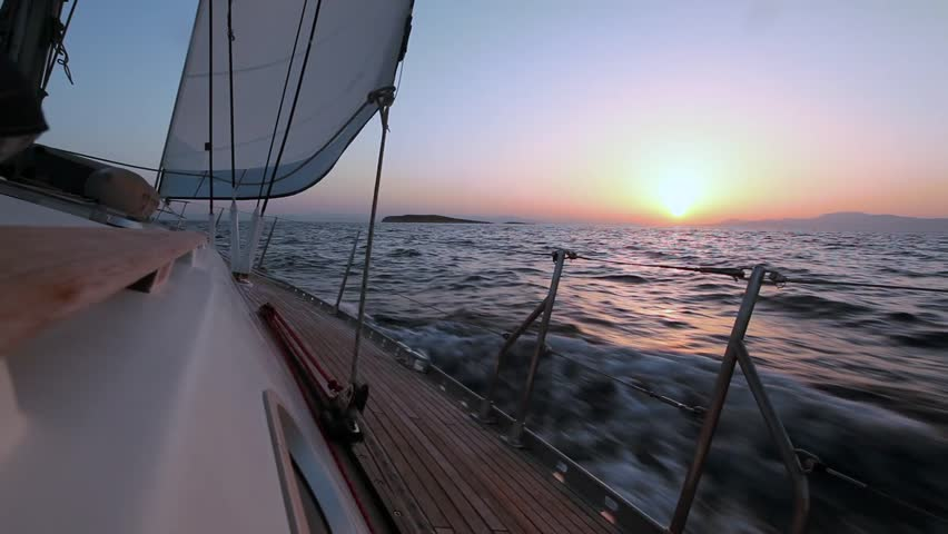 Sailing boat in the wind through the waves during sunset shot in full HD