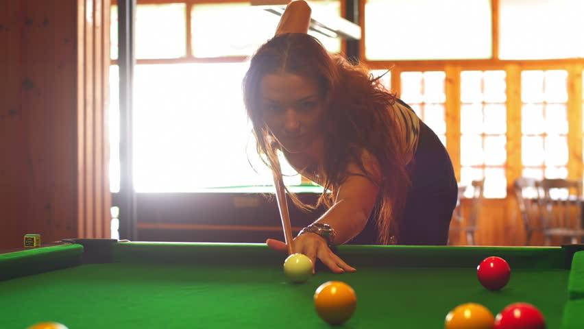A woman plays billiards at a bar