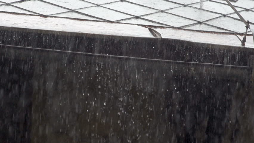 Slow Motion Of Heavy Rain. Raindrops Pouring Off The Roof Of A Building.