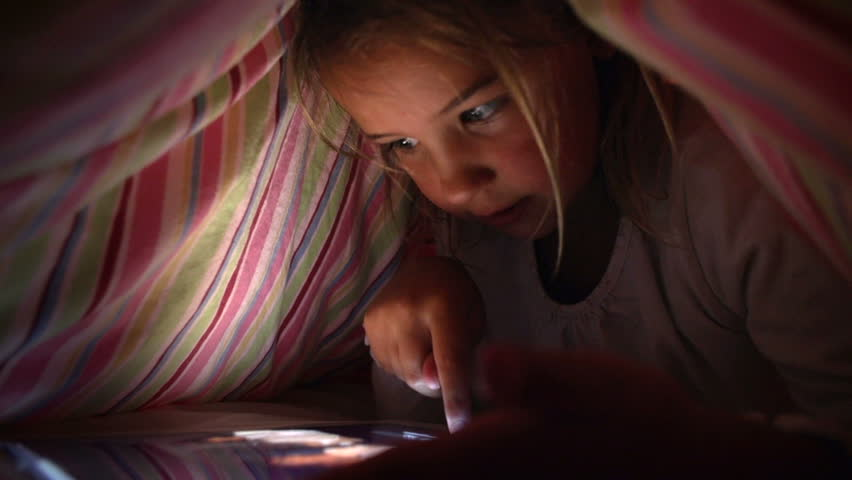 Young girl hiding under duvet to use digital tablet device late after bedtime