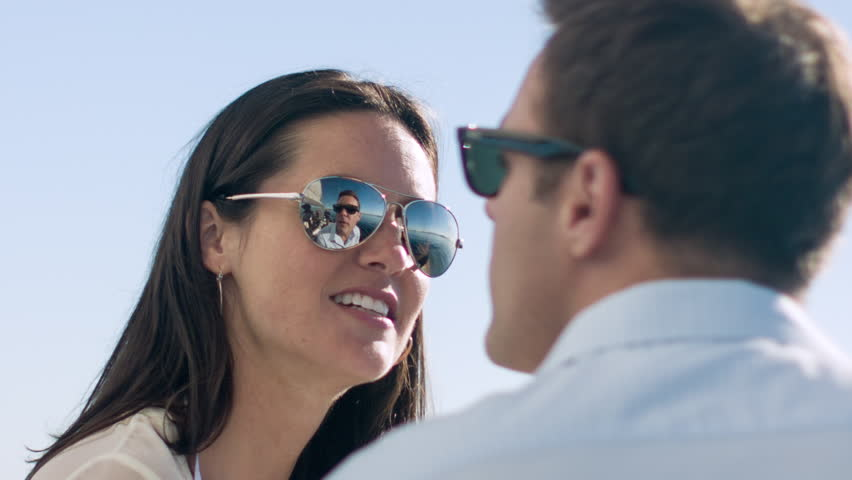 55e725db0a66 Close up of a young woman wearing mirrored sunglasses while sailing on the  Puget Sound in Seattle, Washington. Her male companion and some of the boat  can ...
