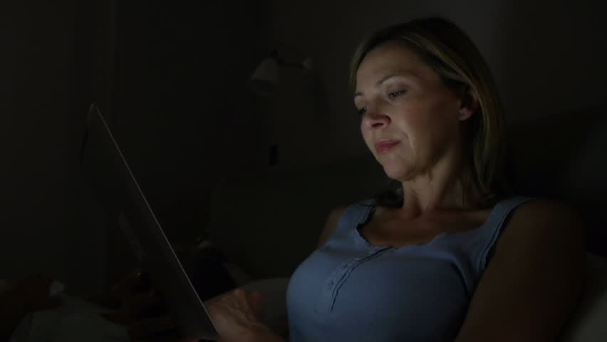Sleepless middle aged reads on digital tablet at night while husband sleeps