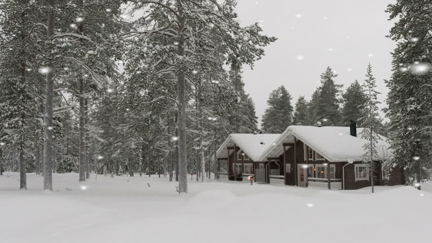 Beautiful traditional snow-covered log cabin surrounded by a forest of evergreen fir trees and thick snow with falling snowflakes giving a scenic wintry Christmas feeling