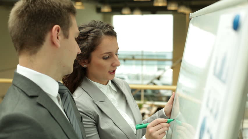Businesswoman explaining something to her colleagues on whiteboard | Shutterstock HD Video #4890179