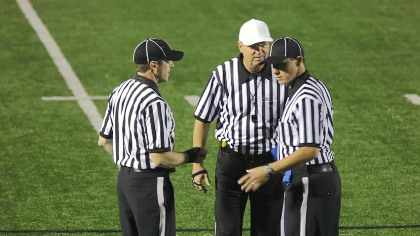 Three football referees stand in a group and discuss a call. The head ref signals pass interference as the penalty