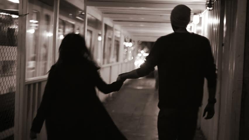 Couple running away at night