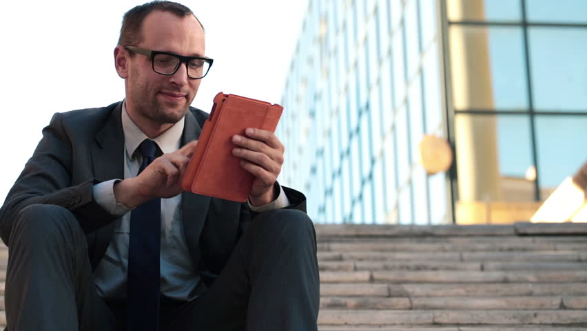 Young businessman with tablet computer sitting in the city  | Shutterstock HD Video #4894493