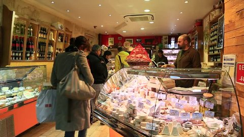 PARIS, FRANCE - OCTOBER 16 : Vendor helps female customer to choose her cheese in a French cheese shop with dozens of kinds of cheese at rue Montorgueil on October 16th 2013 in Paris, France