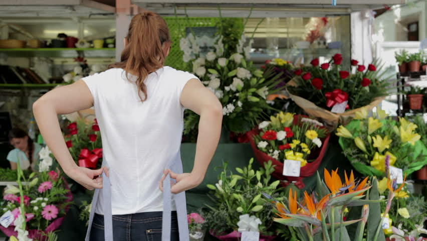 Rear view of a young florist woman tying up her apron bow while getting ready for working at her flowers store with bouquets and floral gifts, outdoors.