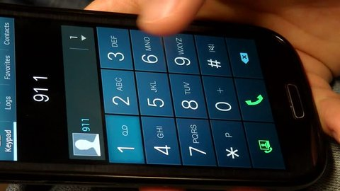 A close up of a phone and a hand dialing 911