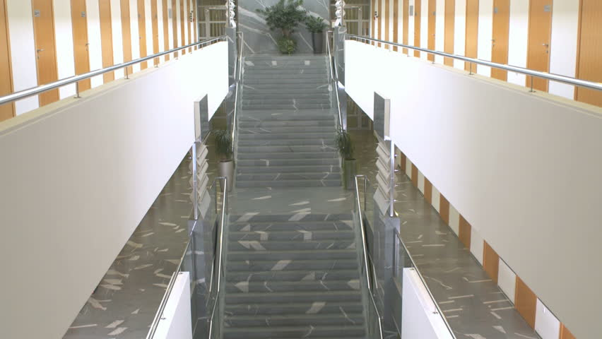 Edited Wide Shot Of A Businessman Ascending The Stairs In Prominent Office