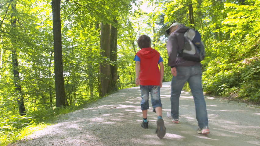Crane Rear View Shot Of Grandfather And Grandson Hiking In Green Forrest