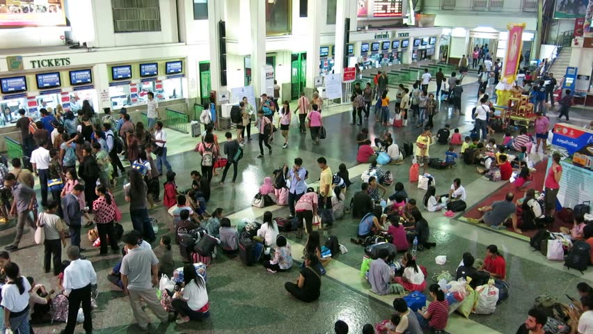 Bangkok, Thailand – October 17, 2013: Thais and tourists queue to buy tickets at Hua Lamphong Railway Station (Bangkok Railway Station), and some sitting on the floor wait for their trains. #4938689