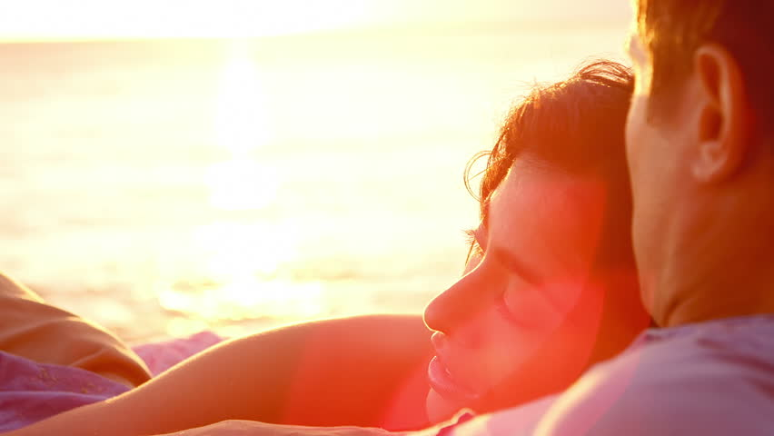 A couple lays in the sand at the beach and look out to the horizon, with lens flare | Shutterstock HD Video #4941449