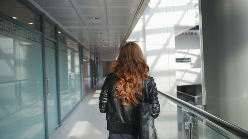 Beautiful girl goes on an office building, she turns around and looks very happy and fun   Shutterstock HD Video #4946519