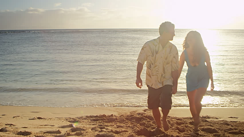An older couple hold hands and stand looking at the ocean from the beach